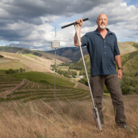 Man stands with a long t-shaped tool in front of a vineyard. The sky is stormy behind him.