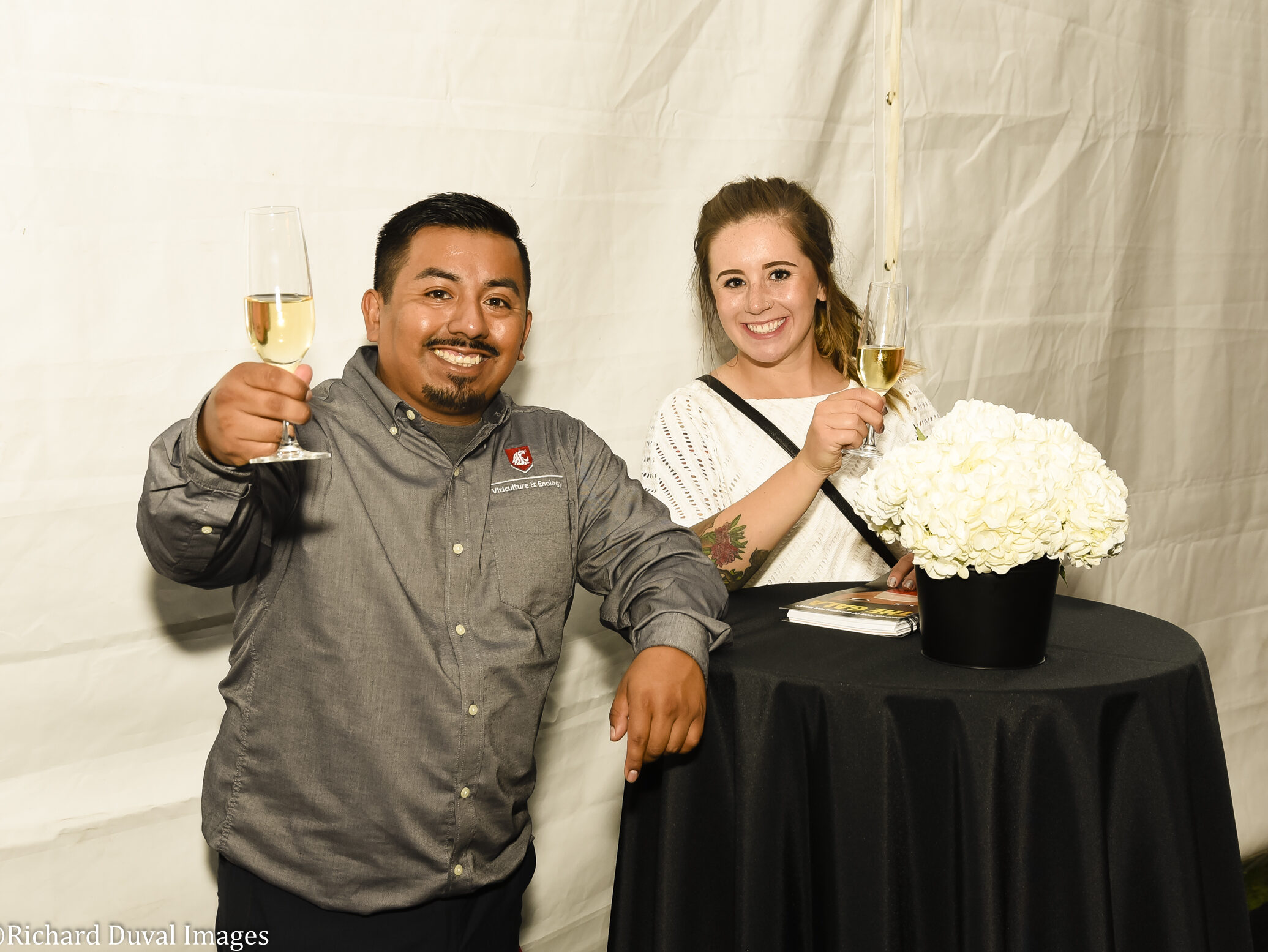 A man and a woman standing at a high table with a black table cloth and white flowers hold a glass of white wine up and smile.