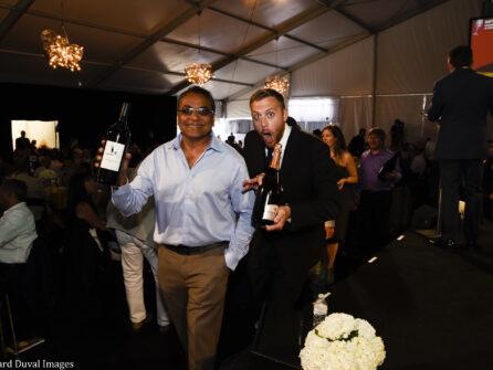 Two men hold bottles of wine in a dark room, one is smiling and one has a faux-surprised expression.
