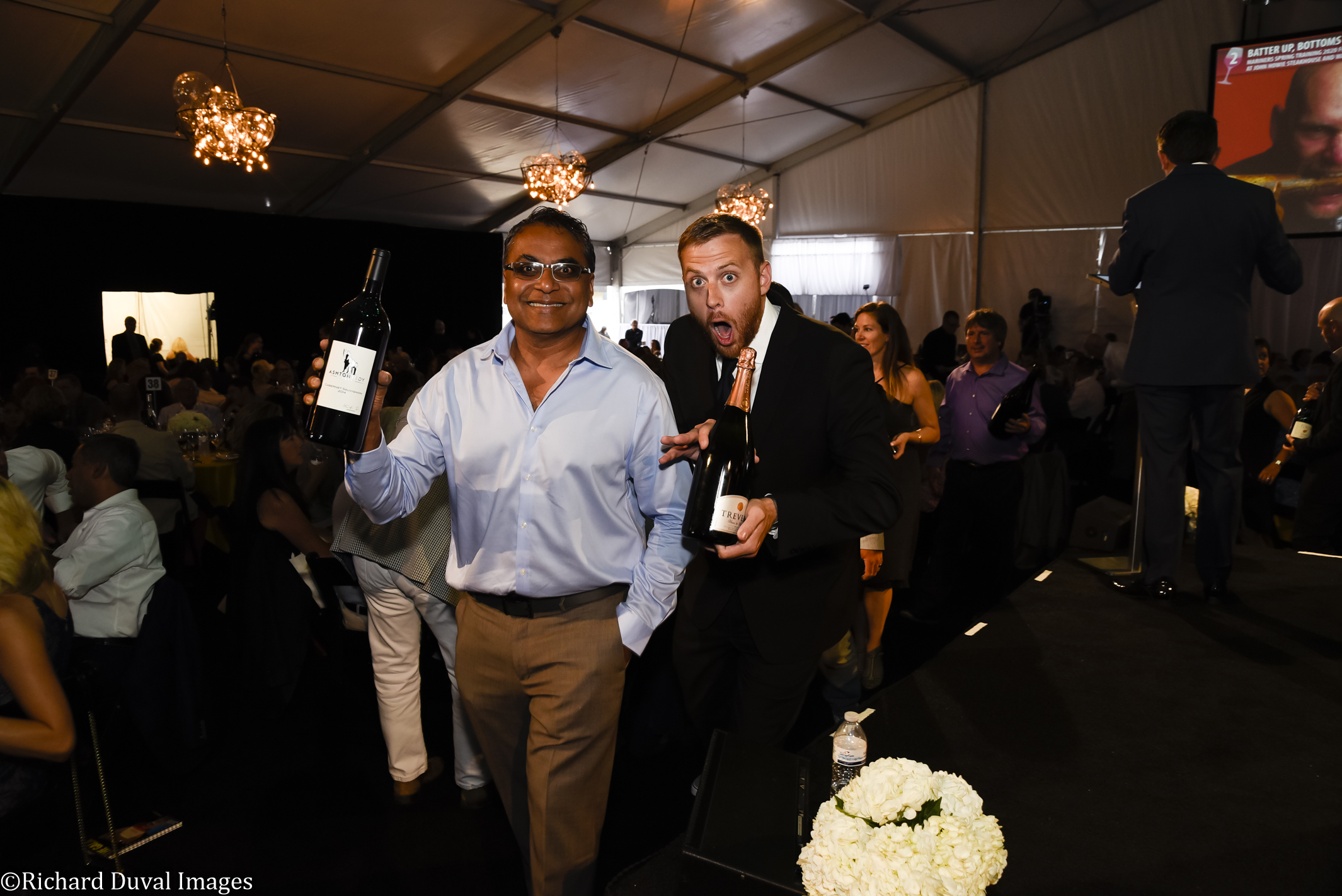 A man in a blue button-up shirt and sunglasses holds a bottle of wine and smiles next to another man in a black suit with a faux-surprised expression. They are in a dark room with people all around them.