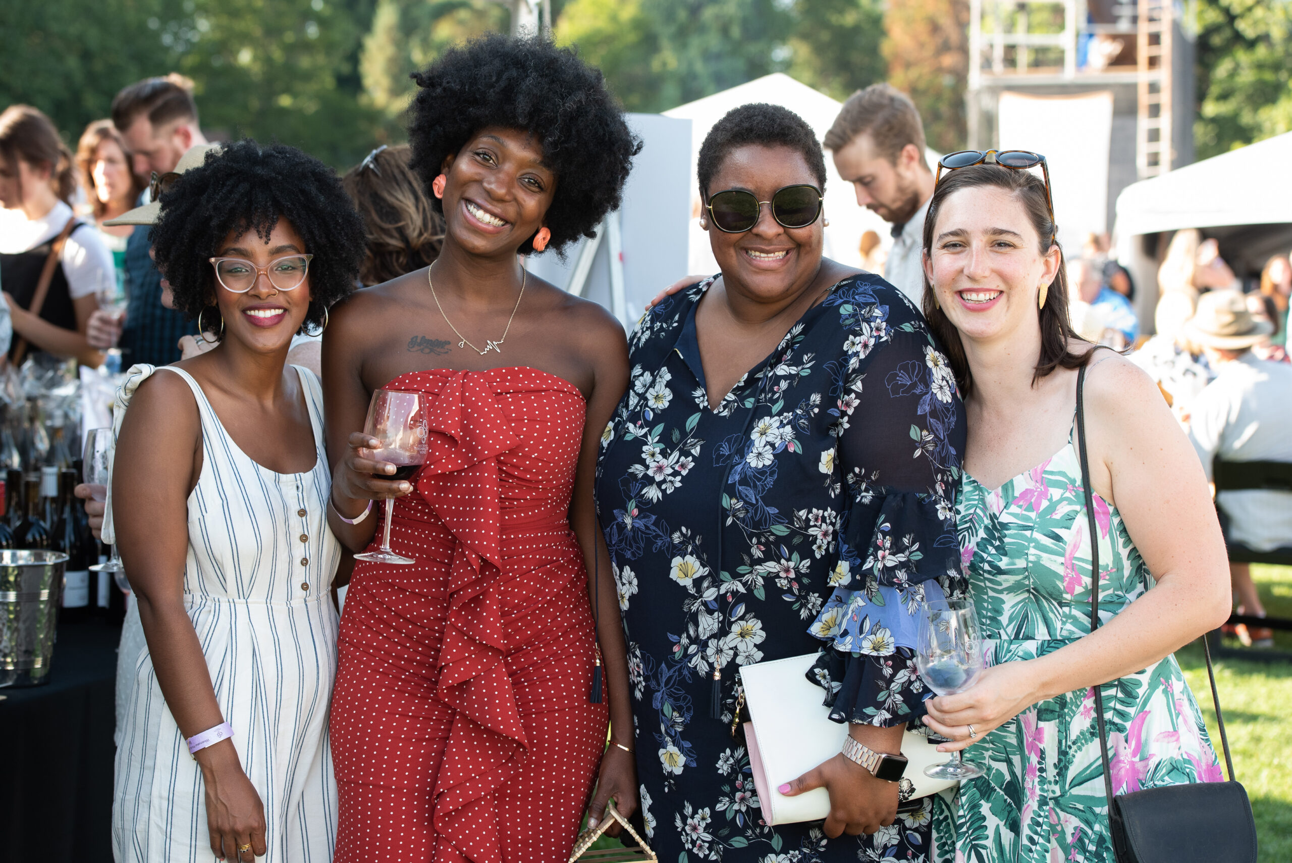 Four women stand together and smile. Two of them hold glasses of wine and they are wearing festive summer dresses. There are people and tents behind them.