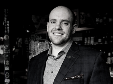 A black and white image of a man (Nick Davis) with short buzzed hair wearing a jacket and collared shirt smiles softly and holds a glass of white wine. The background is a dark room with bottles and a bar.