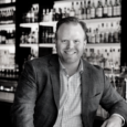 Black and white image of a man seated with his elbow on a bar. He wears a suit jacket and gingham button up shirt and smiles. Shelves of bottles are behind him.