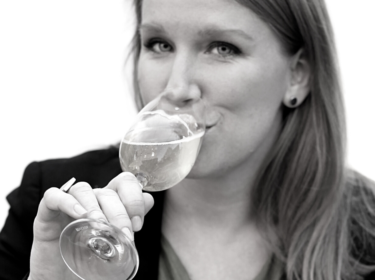 A young woman sips from a glass of white wine. She has long medium dark hair and stud earrings in front of a light background.