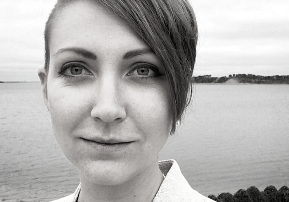 Black and white close-up image of a woman with a side-swept pixie haircut. She smiles wryly and wears a white collared blazer. A large body of water and distant shore are behind her.