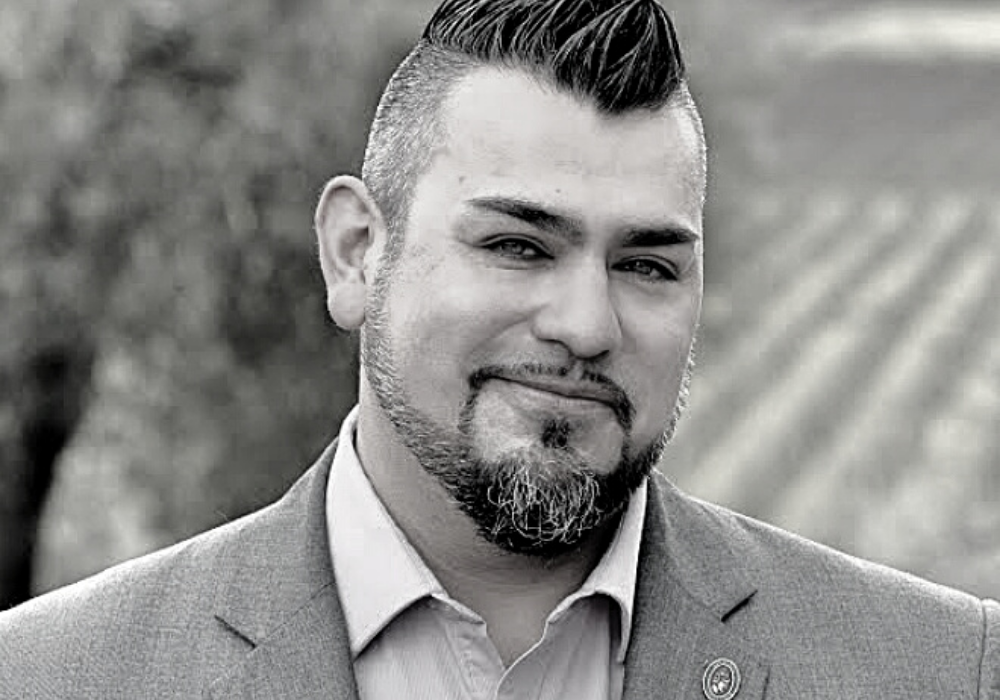 Black and white image of man with dark hair slicked up in a faux-hawk and a dark beard, wearing a grey jacket and collared shirt. There are rows of vines in the background.