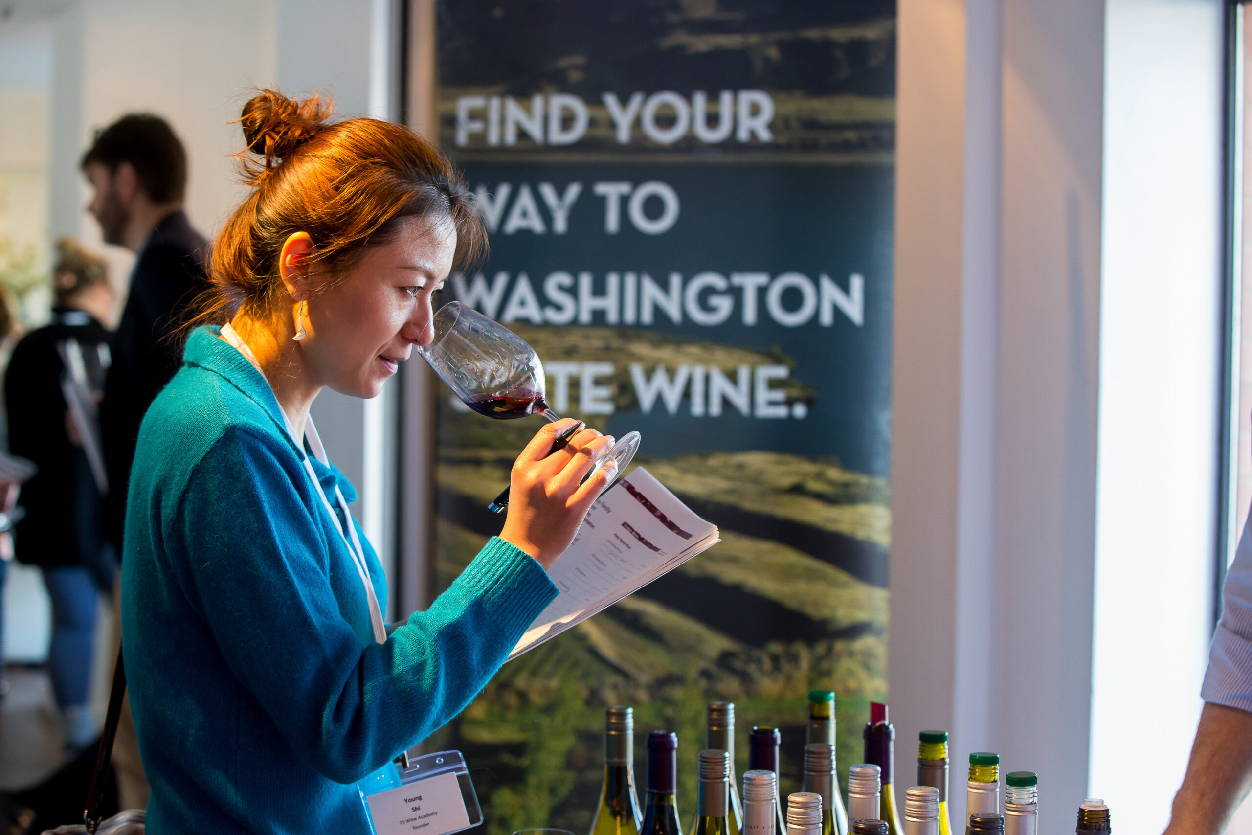 A woman in a blue sweater with dark hair in a bun holds a glass of red wine to her nose and holds a sheet of paper in her other hand. A banner with the words