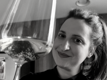 Black and white image of a woman with dark lipstick and long dark hair tied up, holding a glass of white wine to the camera. She is indoors with a dark wall behind her.