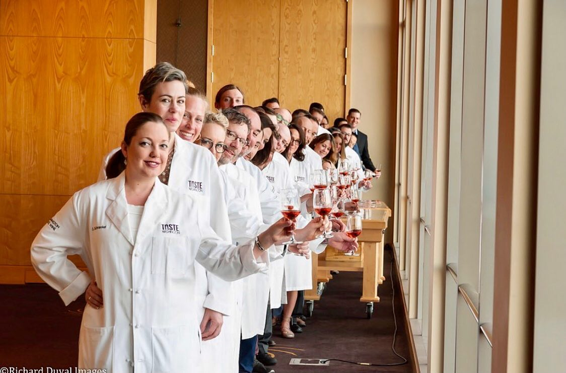 People in white coats stand in a line with glasses of wine in their left hands. Wood paneled cabinets are behind them and tall windows are to the right.