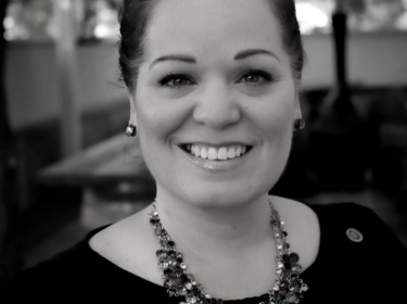 Black and white image of a woman with dark hair up and wearing a large necklace and dark shirt. She smiles and stands in front of tables and trees.