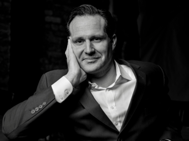 Black and white image of a seated man with his hand resting on his face. The man wears a black suit jacket and white button up shirt and smiles softly.