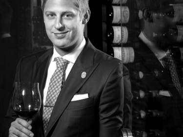A man with scruffy blond hair wearing a suite and tie smiles and holds a glass of red wine in front of racks of wine bottles