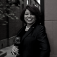 Black and white image of a woman with chin-length dark hair and wearing a black suit jacket leans against a stone wall outdoors with a glass of wine in her hand.