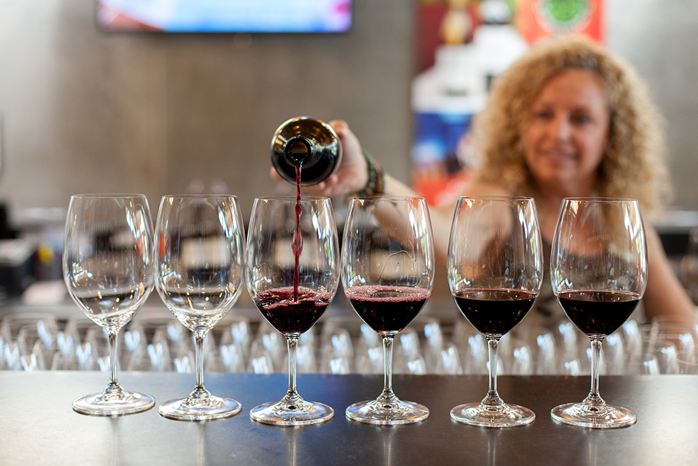 A woman pours red wine into a set of wine glasses. She is smiling and out of focus.