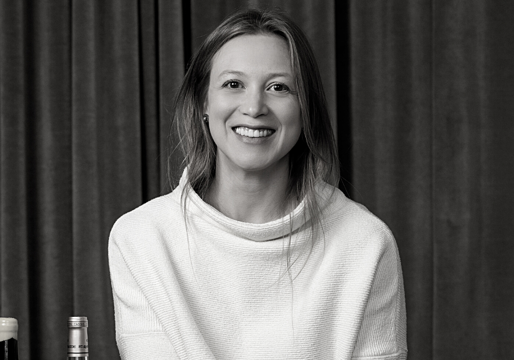 Black and white image of a young woman with light hair smiles broadly and wears a loose white sweater. She is seated in front of a velvet curtain.