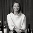 Black and white image of a young woman with light hair smiles broadly and wears a loose white sweater. She is seated in front of a velvet curtain with several bottles on a table around her.