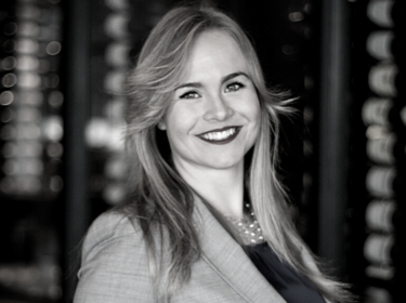 A woman with long blond-brown hair with dark lipstick smiles and holds a glass of red wine. She stands in front of racks of wine bottles and wears a light colored jacket.