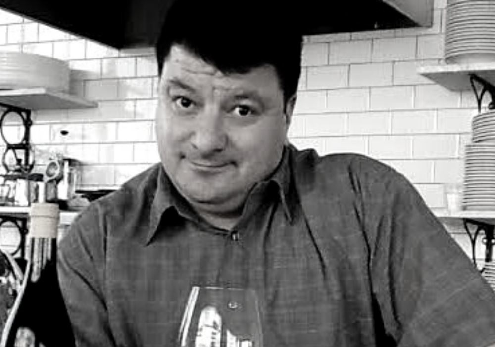 black and white image of a man (Lenny Rede) with short dark hair holds a glass of red wine resting on a counter. A wall of white subway tiles are behind him.
