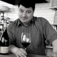 black and white image of a man (Lenny Rede) with short dark hair holds a glass of red wine resting on a counter next to a bottle of wine. White subway tiles and shelves with plates are behind him.
