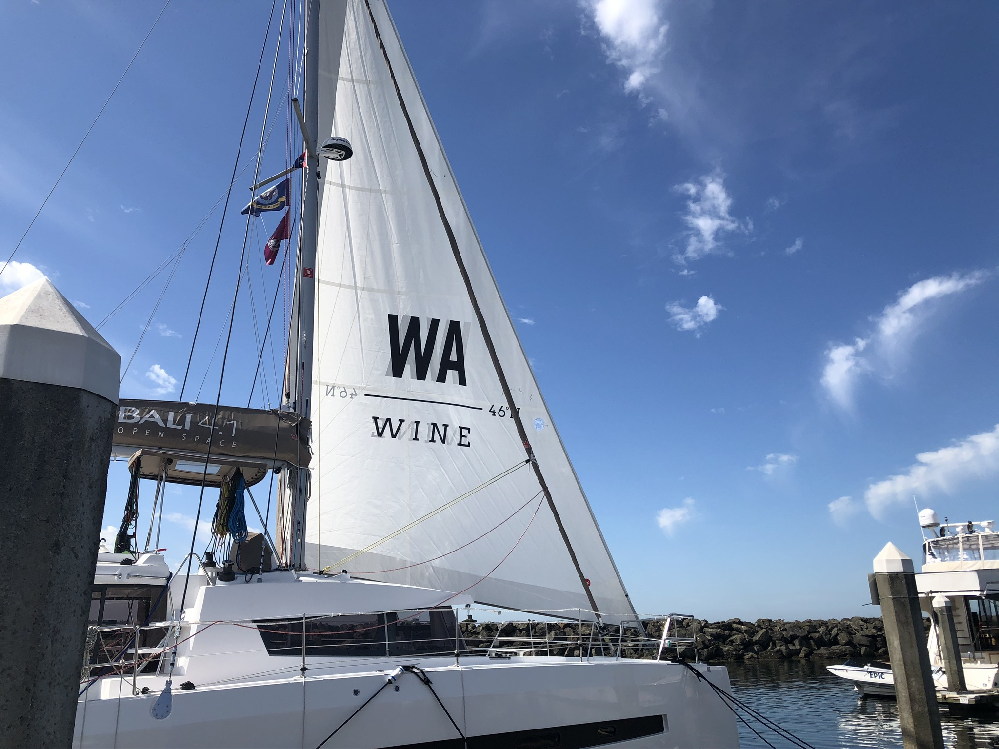 A white sail with a black WA Wine logo on a white sail boat, in front of a bright blue sky.
