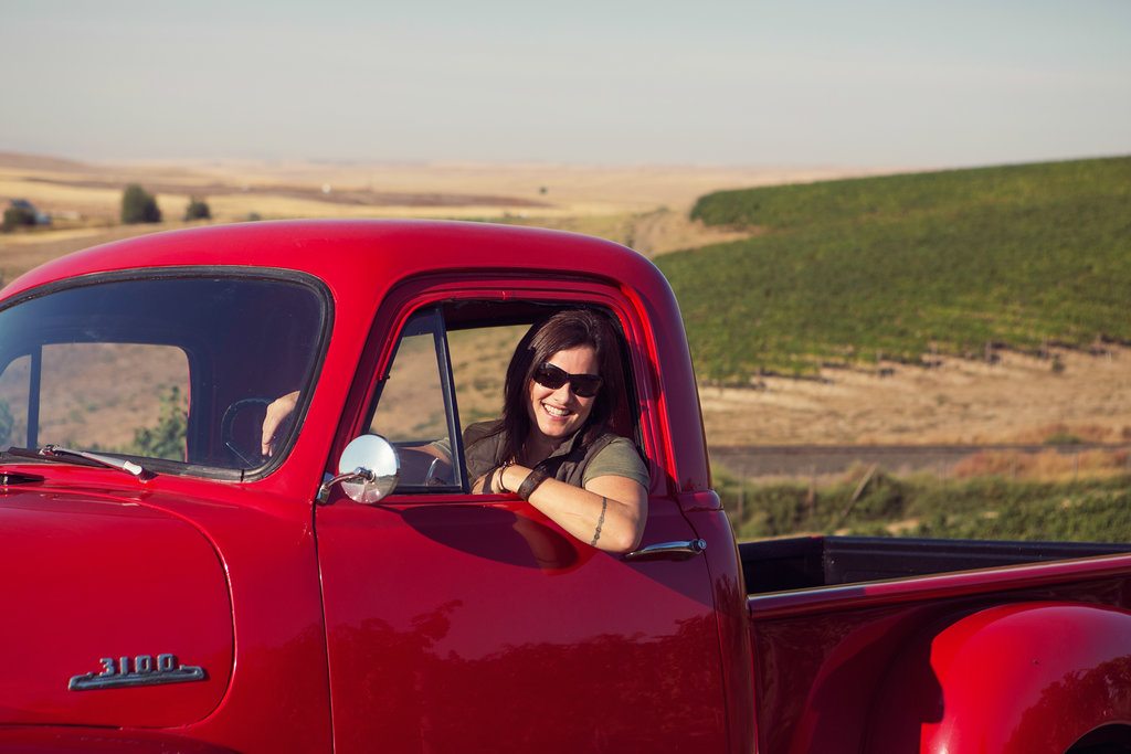 Woman leans out the driver's seat window of a vintage red pick-up truck. Green vines and tan fields are in the background.