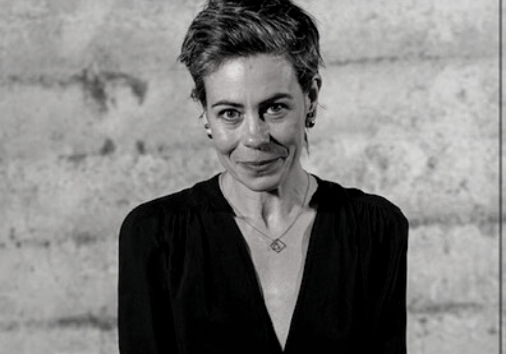 Black and white image of a woman with short wavy hair wearing a dark v-neck shirt. She smiles and stands in front of a light stone wall.