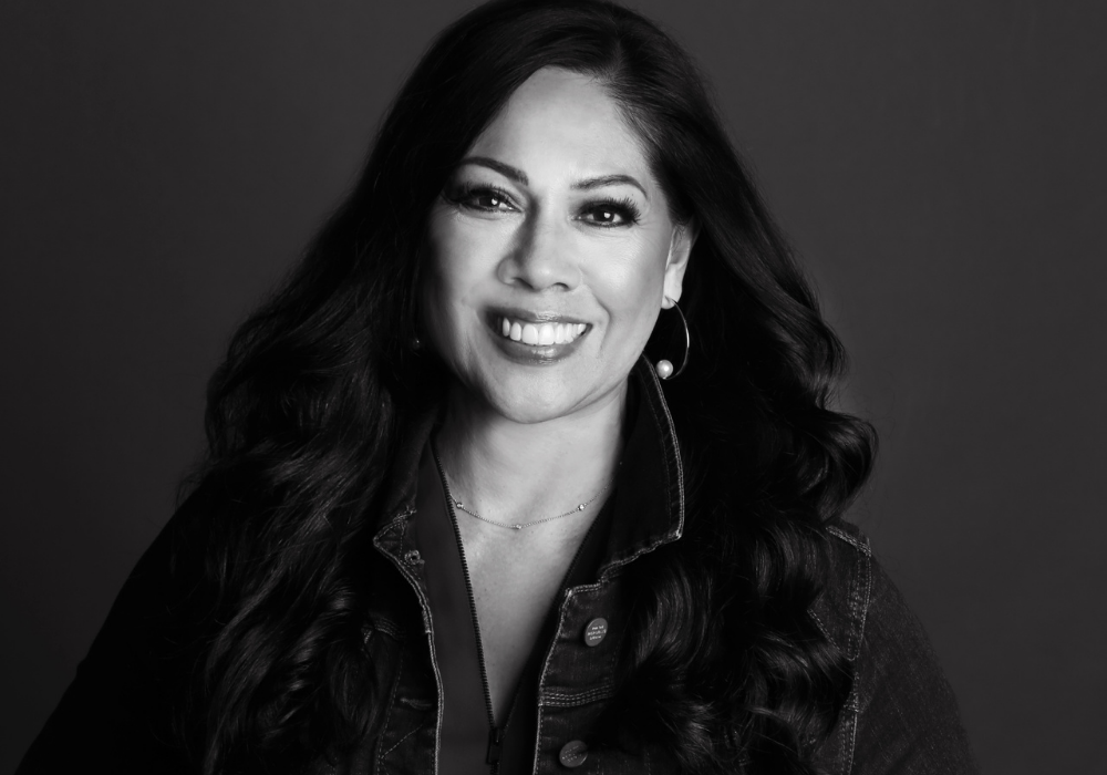 Black and white image of a woman with dark long hair and dark eyes, wearing a black jean jacket and standing in front of a dark background.