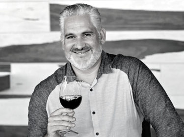 Black and white image of a man with grey and white hair and short beard, smiling and holding a glass of red wine. He wears a shirt with dark sleeves and white front with buttons.
