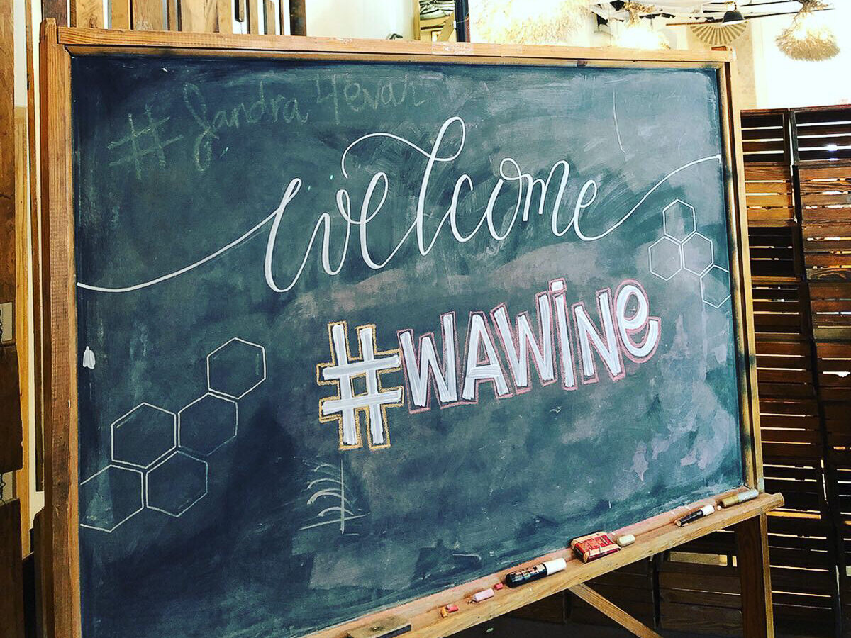 """A chalkboard sign in a wood frame with the words """"Welcome #WAwine"""" written on it."""
