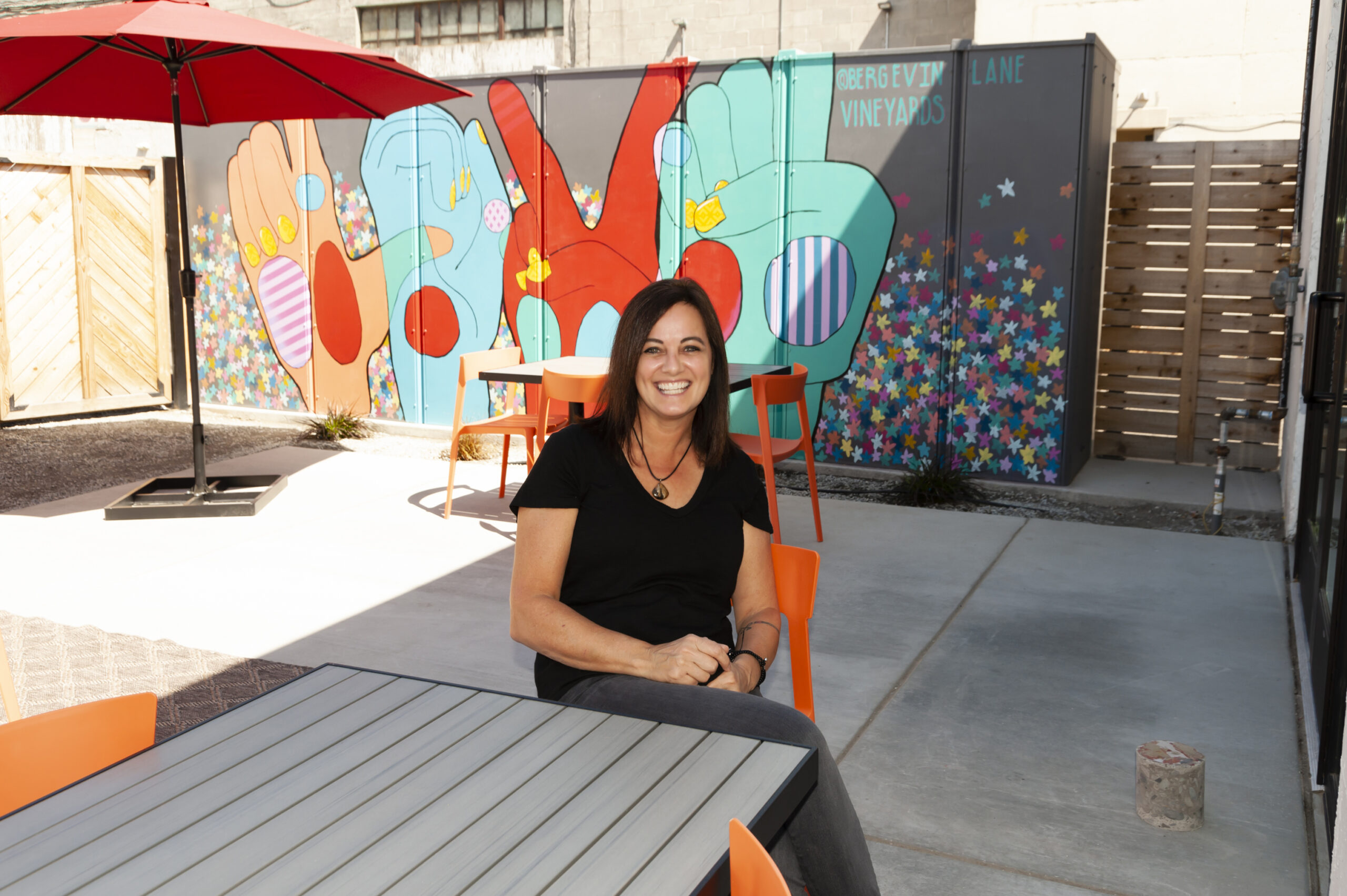 Woman with dark hair sits at a picnic table in front of a red, blue, and grey mural of hands, with Bergevin Lane Vineyards written on the wall.