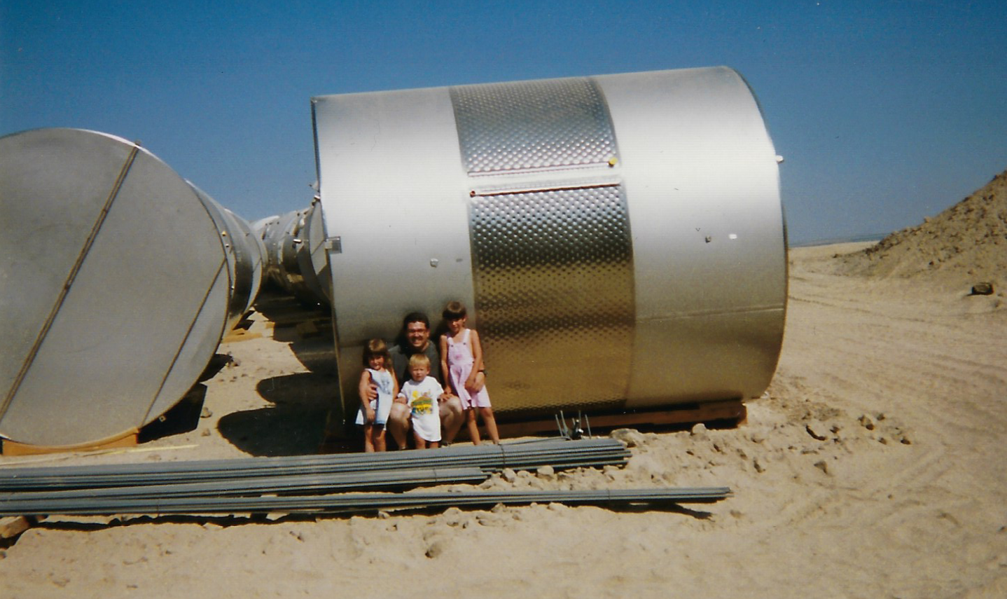 A man sits with three young children against a large metal cylinder. The are around them is dry dirt and the sky is bright blue.