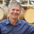 A man with grey hair in a blue button-up shirt smiles in front of a rack of wine barrels.