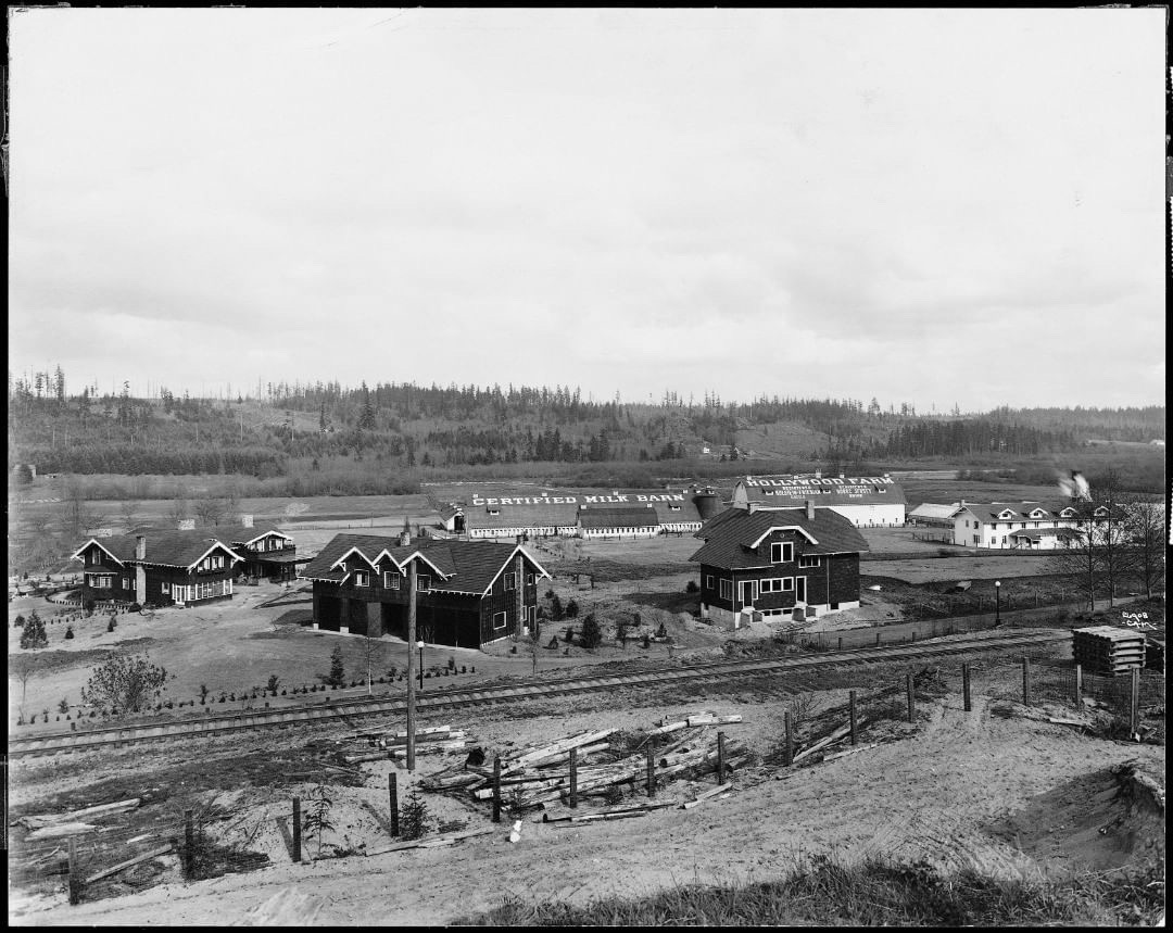 black and white image of dark buildings with white trim, white barn and agriculture buildings, and a railroad track and post fence in the foreground.