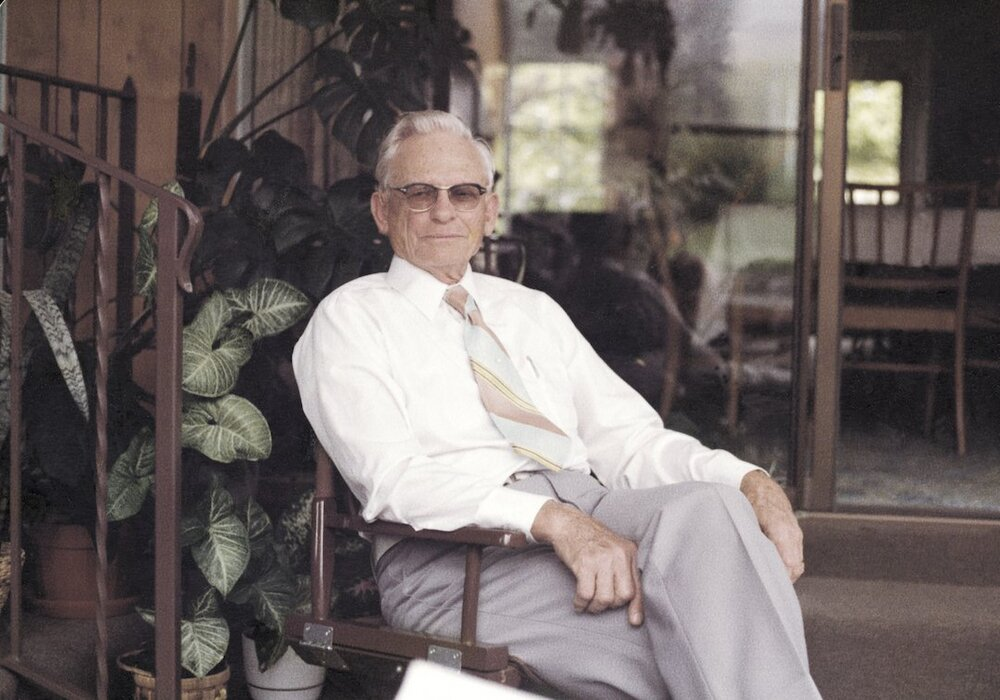 An older man in a white shirt and striped tie and slacks smiles softly and sits in a chair in a sunroom in front of house plants.