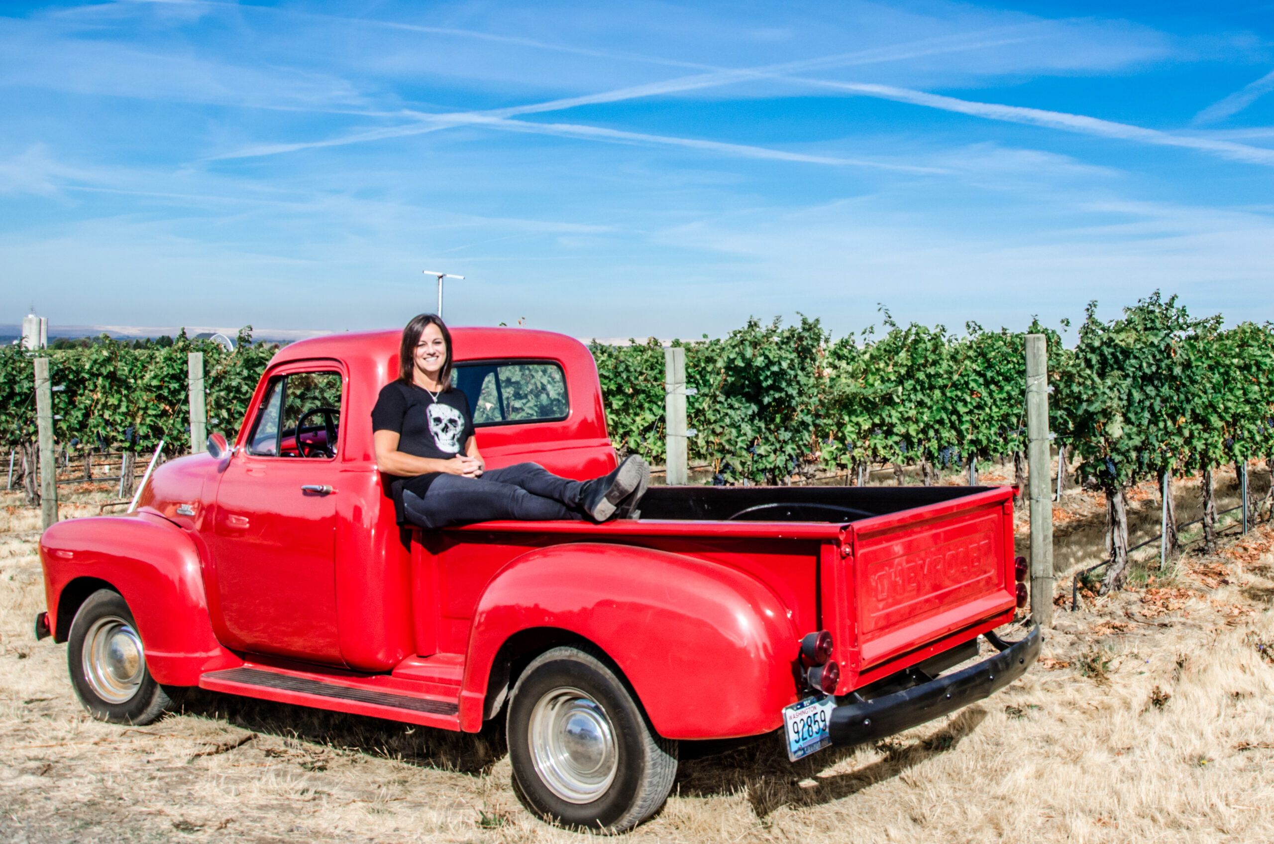 Woman with short dark hair sits on the side of a vintage red pick-up truck in front of green grape vines and posts. Sky above is blue with wispy white clouds.