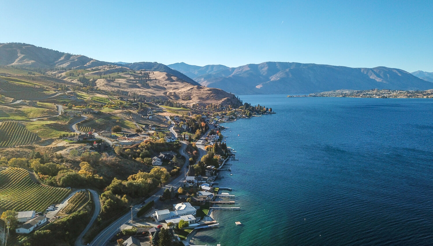 A blue-green lake on the right and shore with buildings and docks on the left, with rolling hills and blue sky in the background
