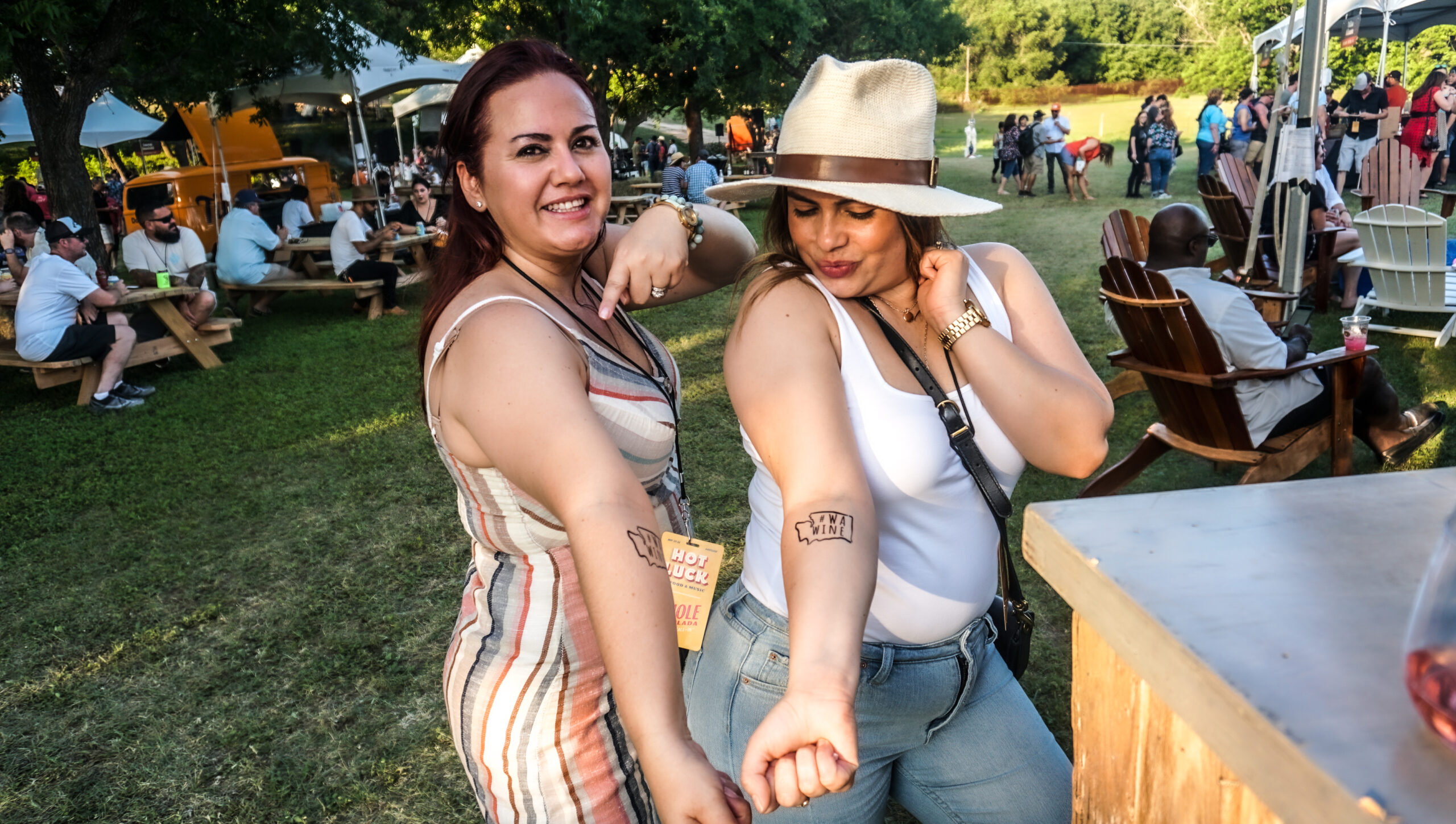 Two women show off their WA Wine temporary tattoos with their arms held out. They are standing on a lawn in front of many other people in chairs and standing.