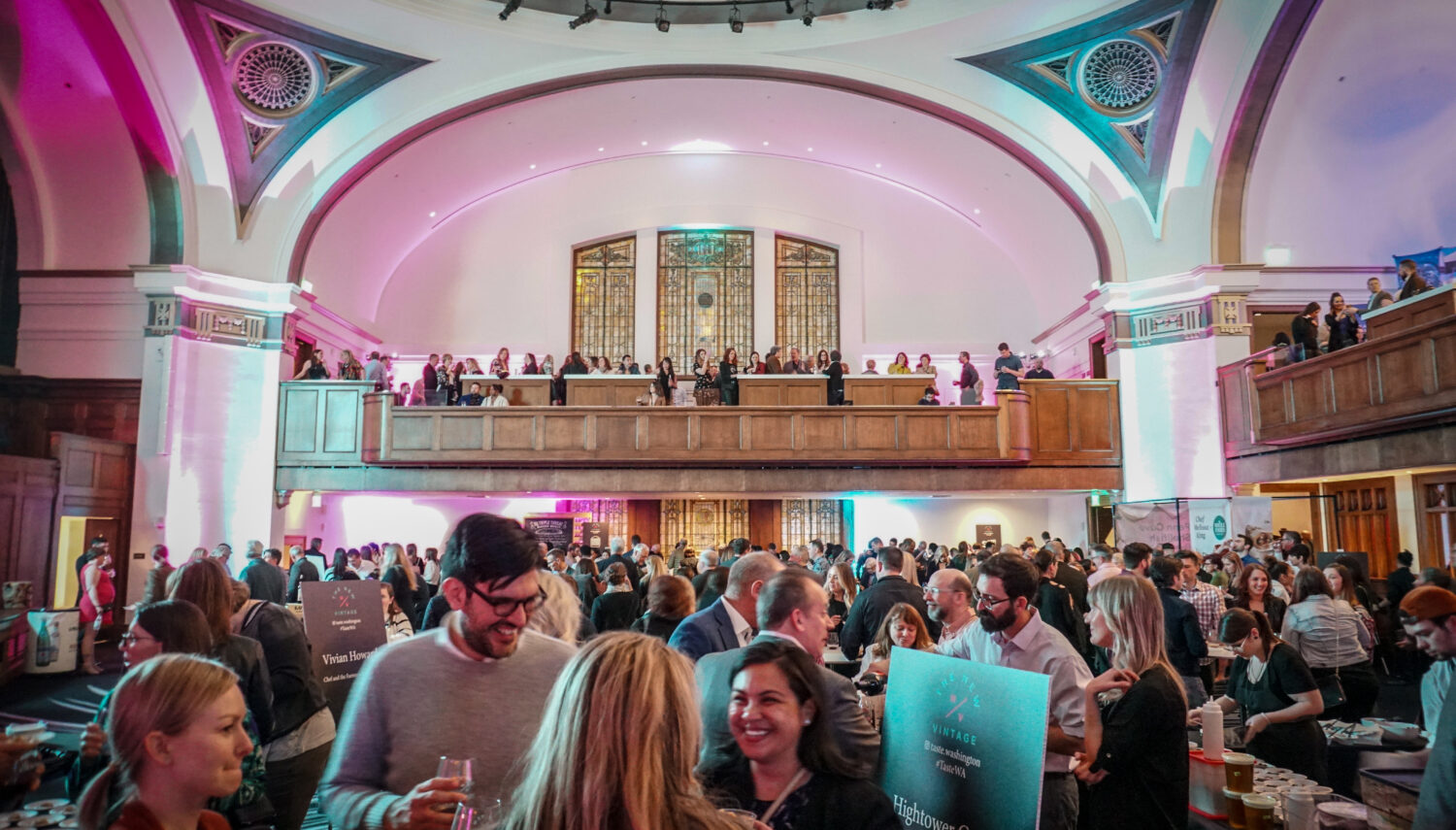 A crowd of people mill in a large room with tall ceilings painted white, pink, and blue.