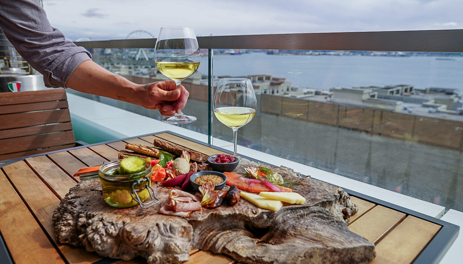 A spread of cheeses, pickles, and meats on a wooden board, with a glass of white wine and another glass of wine held by a hand. The Puget Sound and docks with boats are in the distance.