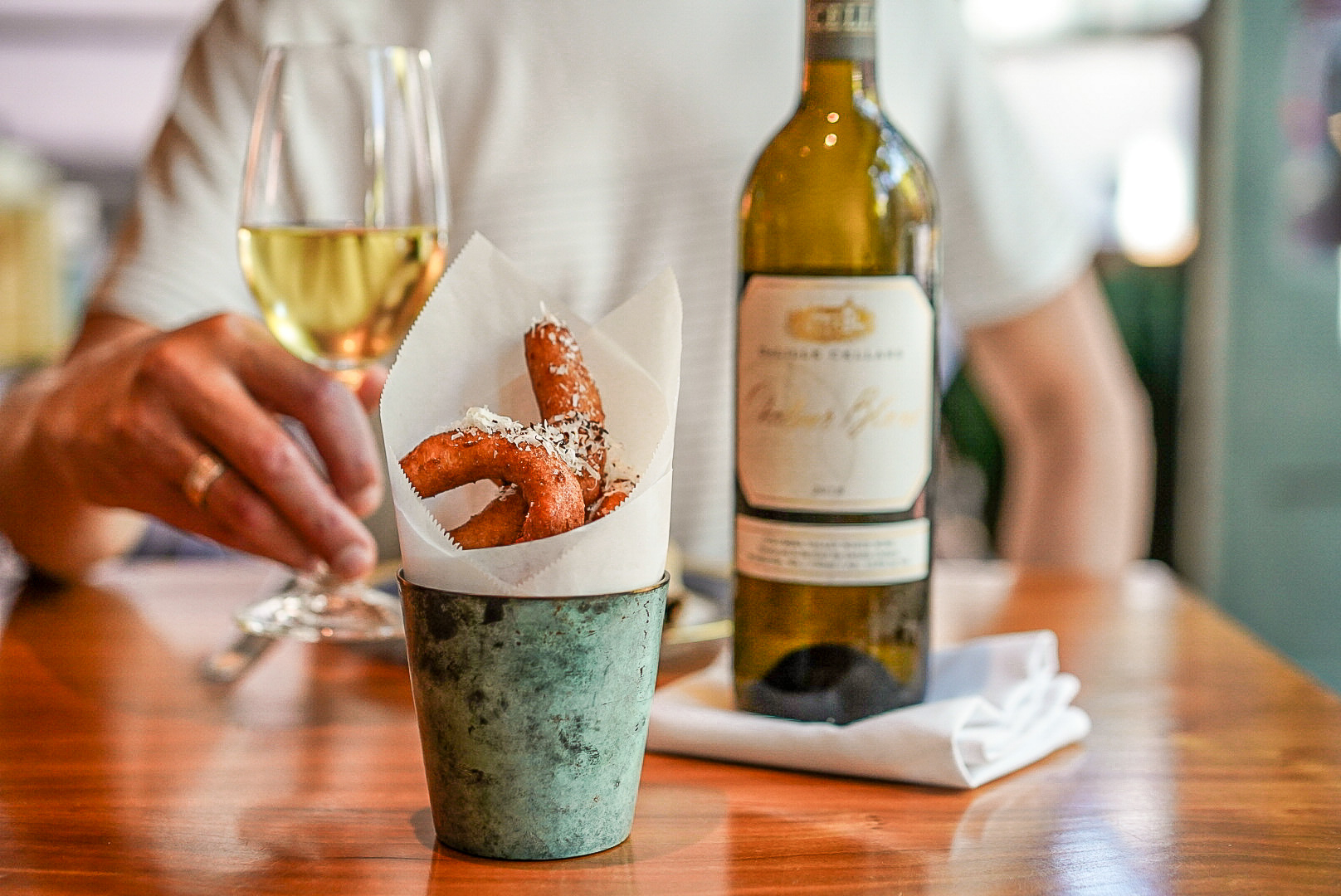 A wooden table with a metal cup lined with parchment paper and holding onion rings, a bottle of wine, and a glass of white wine. A hand holds the glass and a torso is out of focus behind the table.