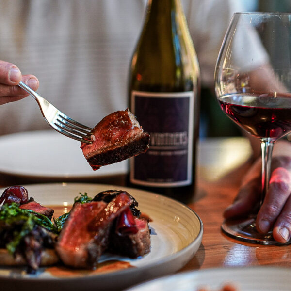 A hand holds a fork with a piece of steak above a plate of food. The person's other hand rests on the base of a glass of red wine, and a bottle of wine sits on the table next to it.