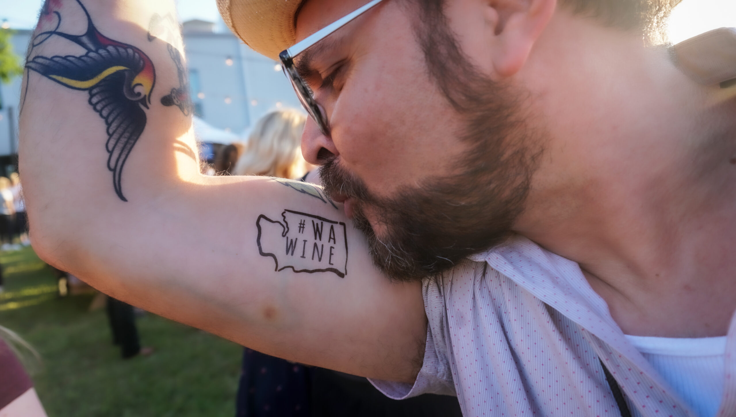 A man with a beard, glasses, and sun hat kisses his bicep where there is a WA Wine temporary tattoo.