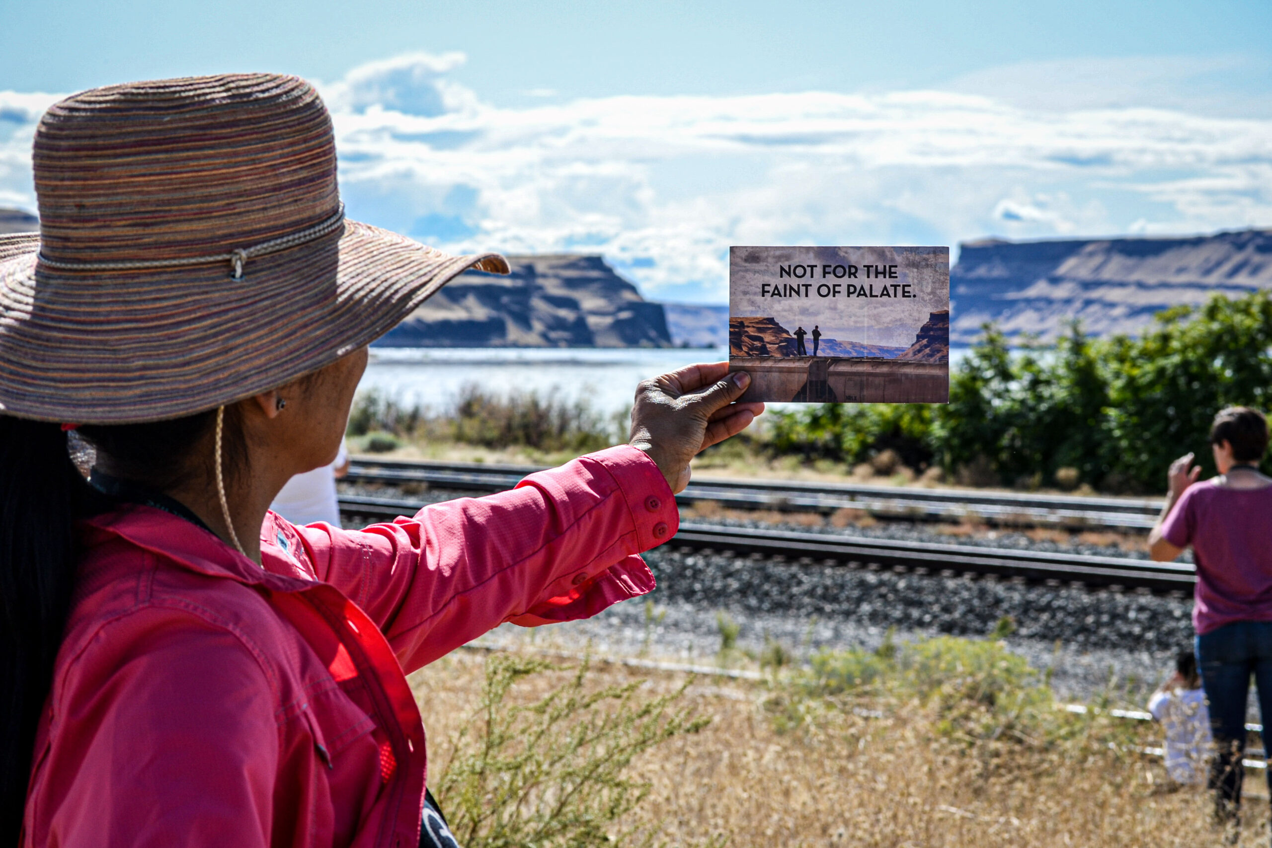 A woman wearing a sun hat and pink shirt holds a postcard up to eye level. Train tracks and a river with steep cliffs are in front of the woman.
