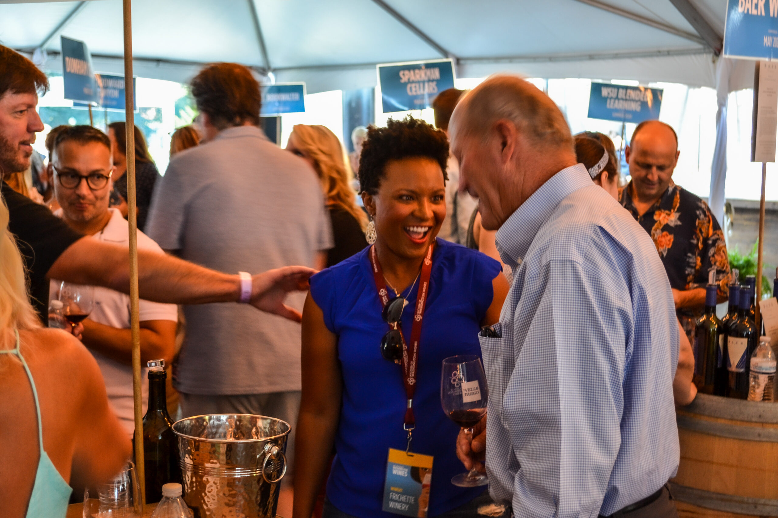A woman with dark hair in a blue shirt talks with a man in light blue button-up shirt in a crowd of people under a tent.