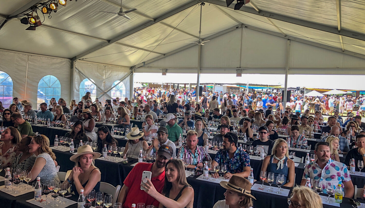 A large group of people sit at long tables facing the camera with glasses of wine in front of each person. A large white tent covers them.