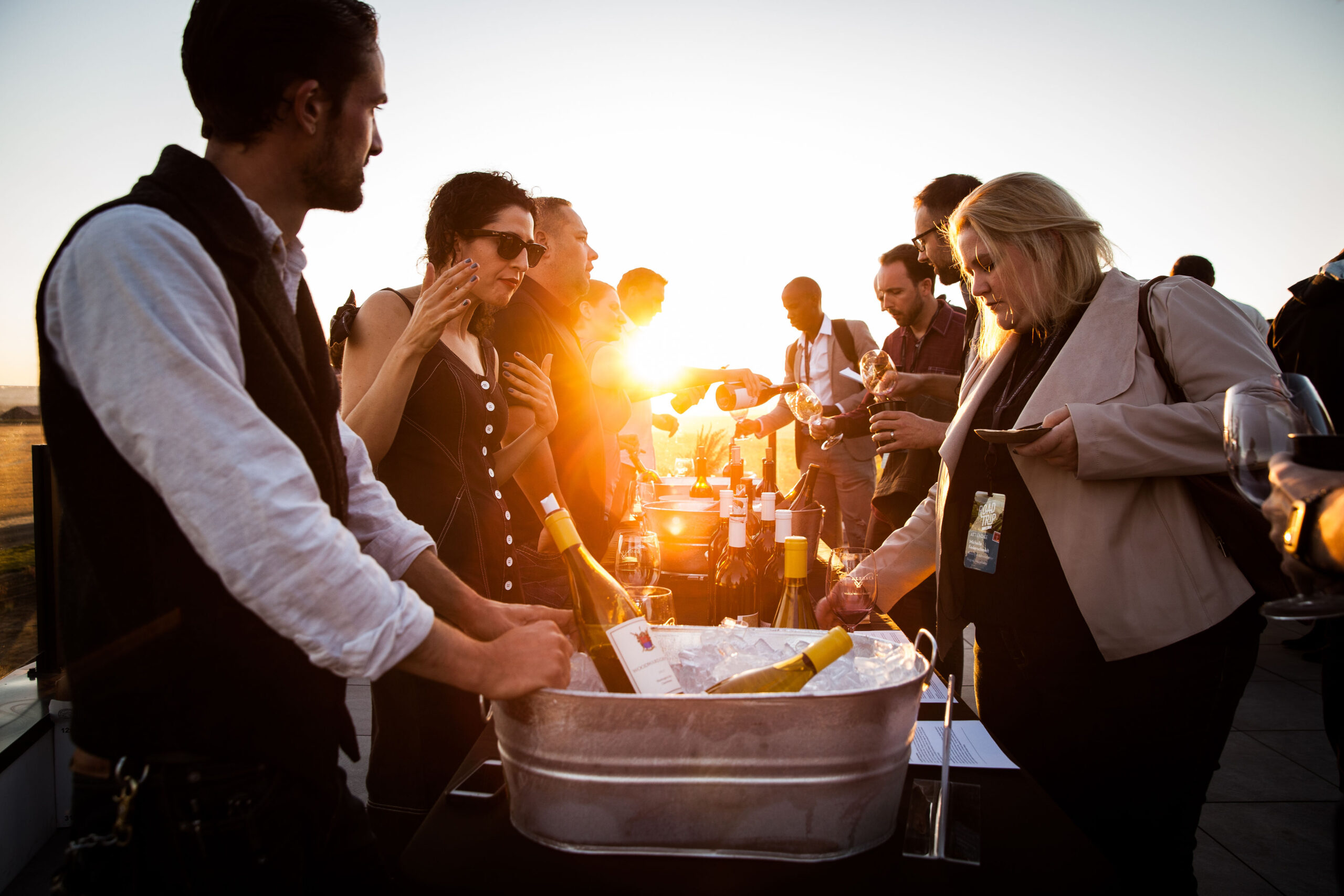 People line two sides of a long table, talking and pouring wine. A bucket of ice and bottles of wine are closest to the viewer and bright yellow sun pierces between the people.
