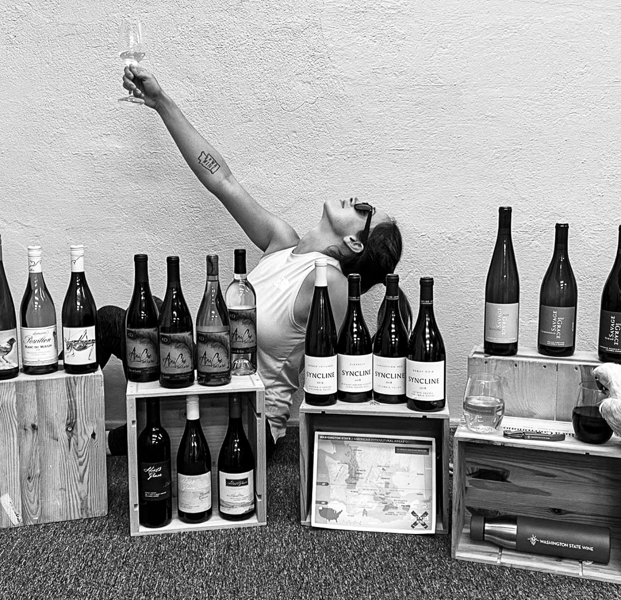 Black and white image of a woman holding a hand with a glass of wine in the air with her head back. She is behind wooden boxes with bottles of wine lined up on them.
