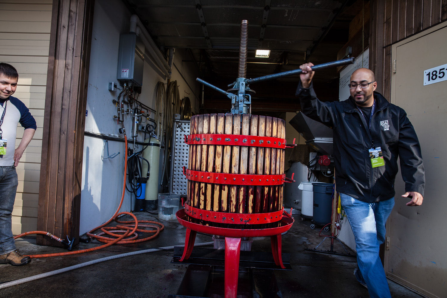A wine grape press made of wood staves and red metal bands, on a red stand. A man in a black jacket pushes the metal bar at the top, in front of room fading to darkness behind.