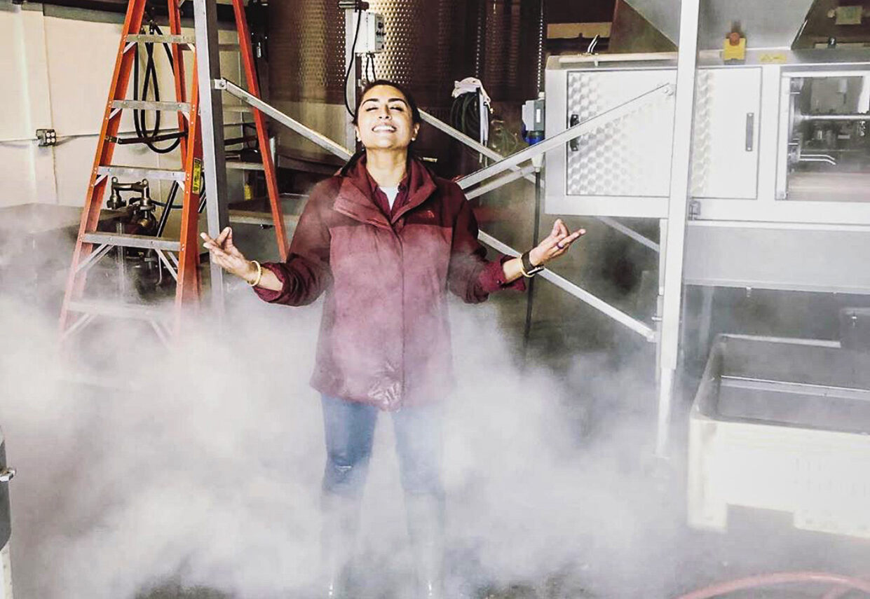 Woman in maroon jacket with her head back and hands raised stands in a cloud of steam in a winery.