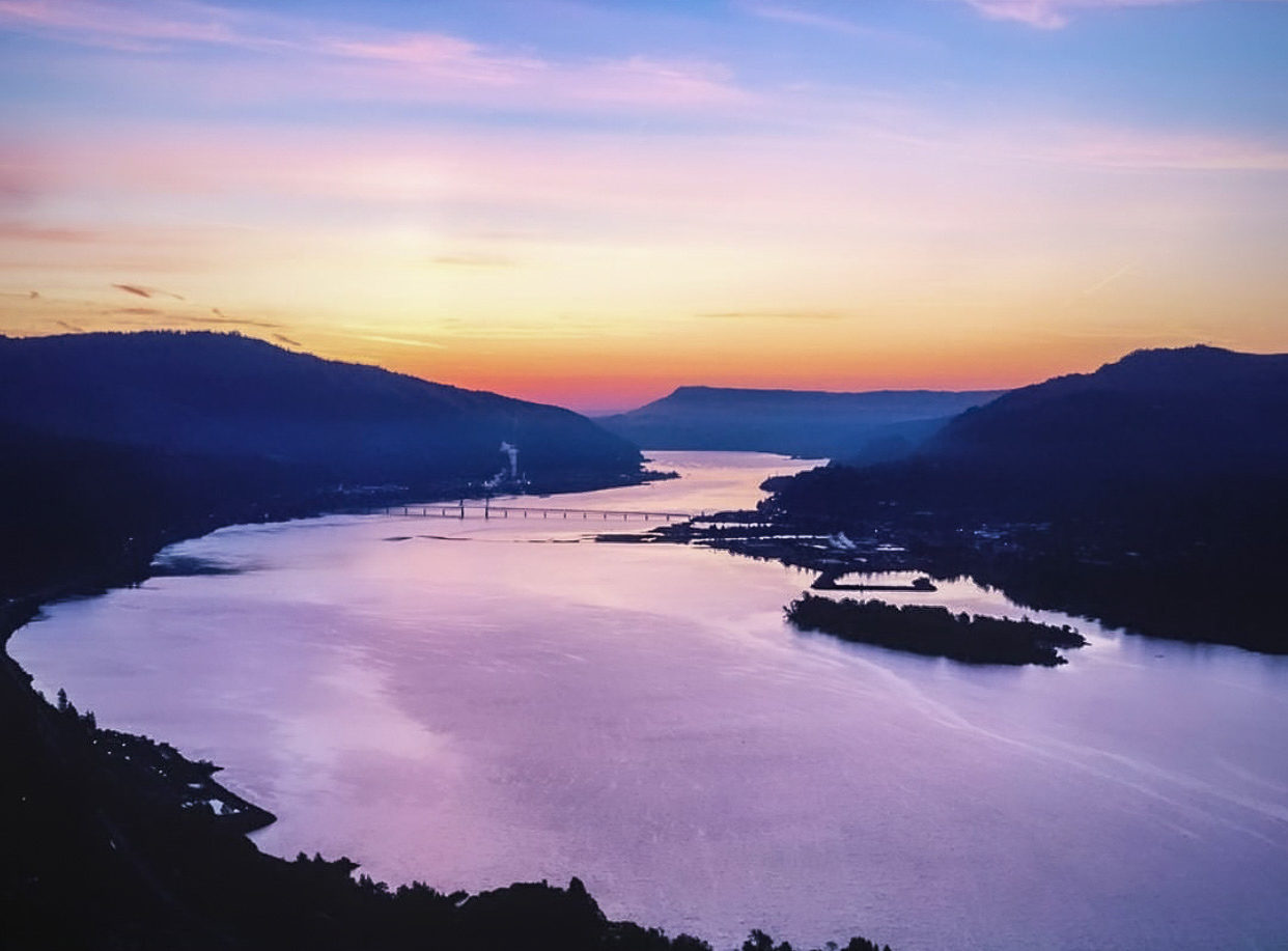 A wide, calm river at sunset reflecting the purple and peach of the sky. Blue hills surround the river.